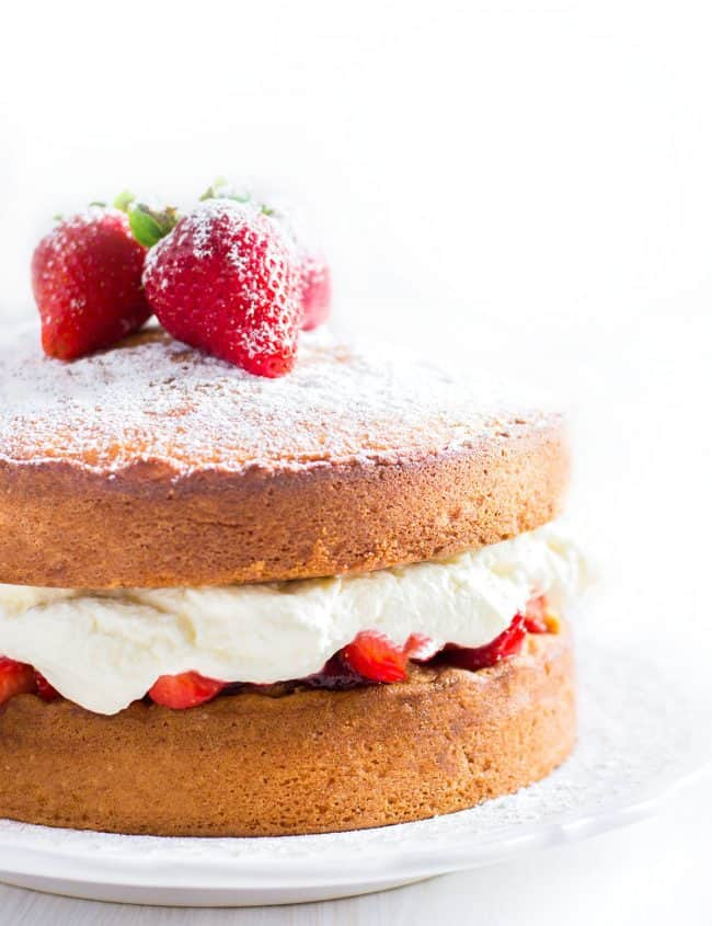 Lemon Sponge Cake filled with fresh strawberries and whipped cream topped with powdered sugar and three strawberries