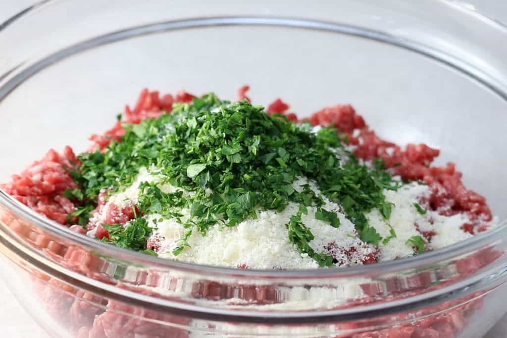 beef, garlic, parsley, and parmesan cheese in a mixing bowl