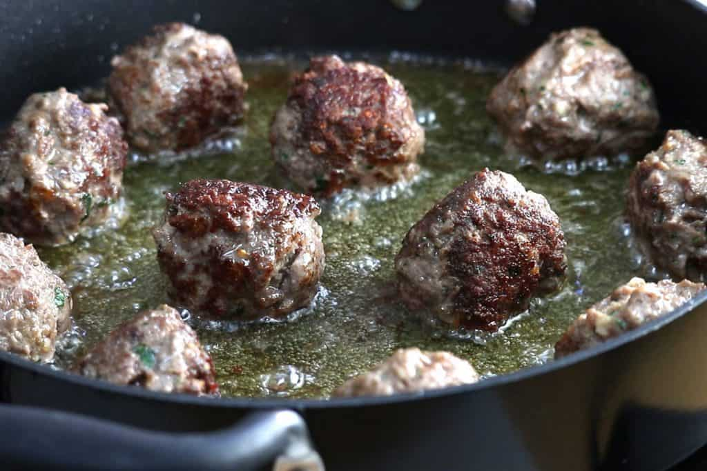 Crisp meatballs cooking in oil in a pan
