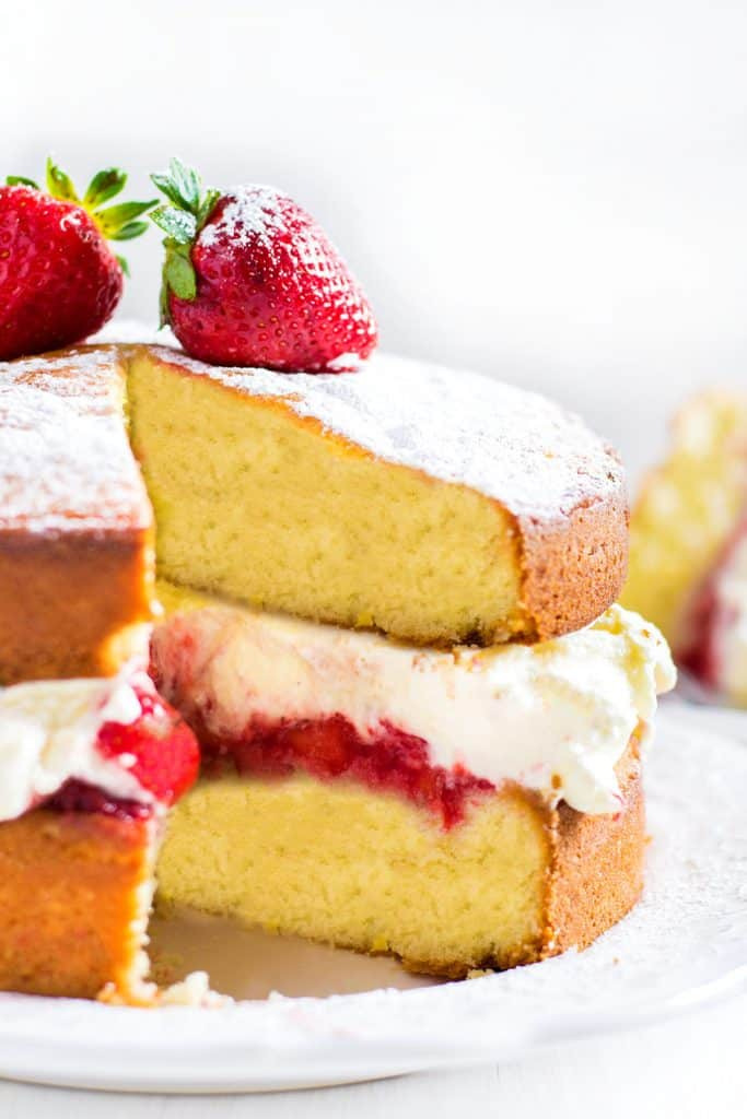 Lemon Sponge Cake filled with whipped cream and strawberries with a slice cut out