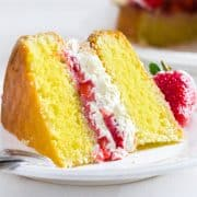 A slice of Lemon Sponge Cake filled with whipped cream and strawberries on a plate with the cake behind it