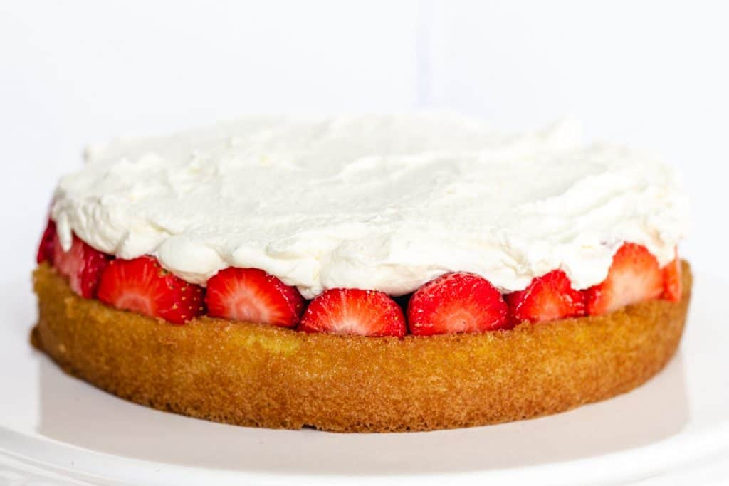 the layer of Lemon Sponge Cake covered with a lyer of strawberries and a layer of whipped cream