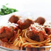 a close up of Spaghetti and Meatballs on a plate with a fork