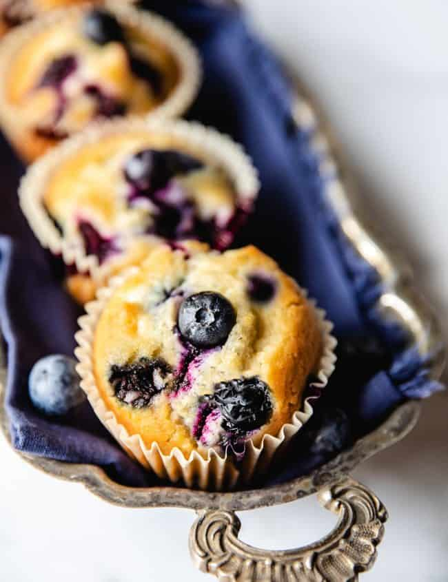 Five Blueberry muffins lined up on a silver tray with an ornate handle