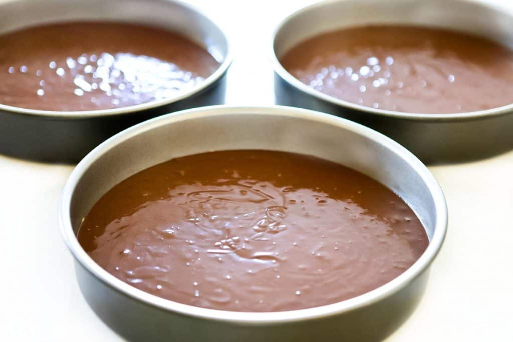 three pans with chocolate cake batter
