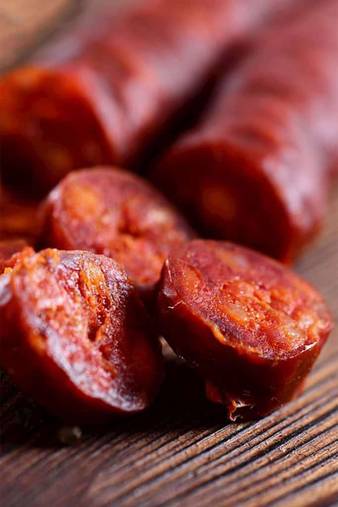 Chorizo sausave cut into slices on a cutting board
