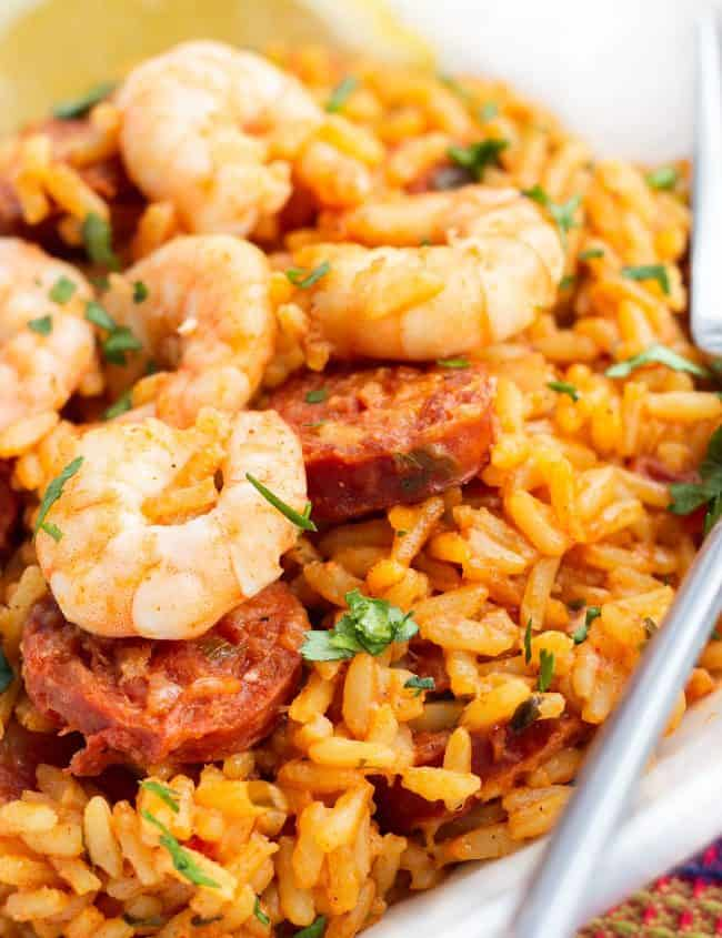 A dish of yellow rice topped with sausage and shrimp