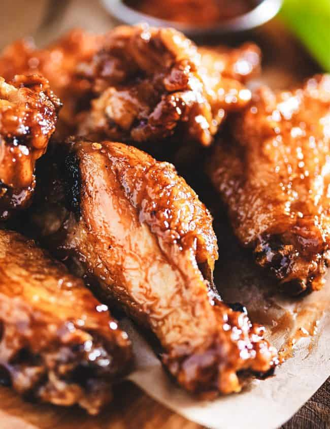 Chicken wings on a wood block with dipping sauce in the background