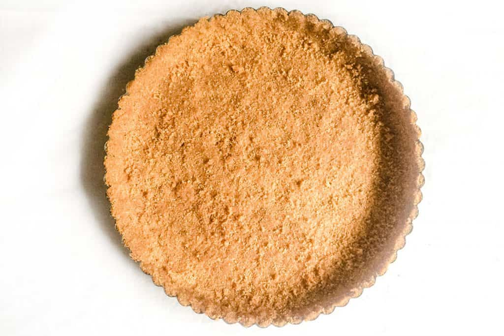 A baked graham cracker crust still in the pan