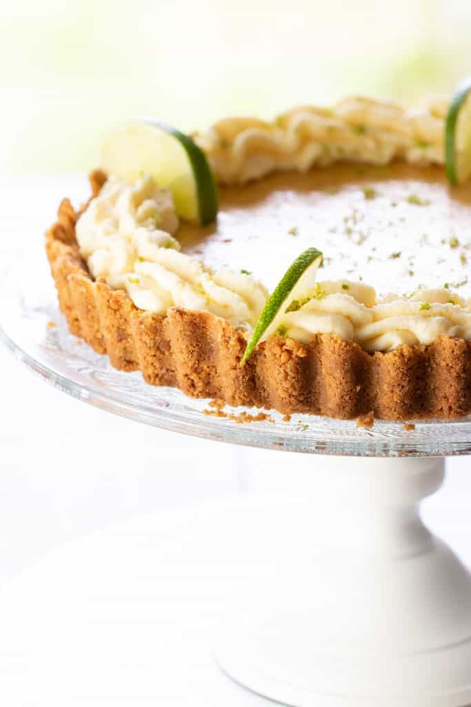 A key lime pie swirled with whipped cream around the edge and garnished with lime slices and zest.