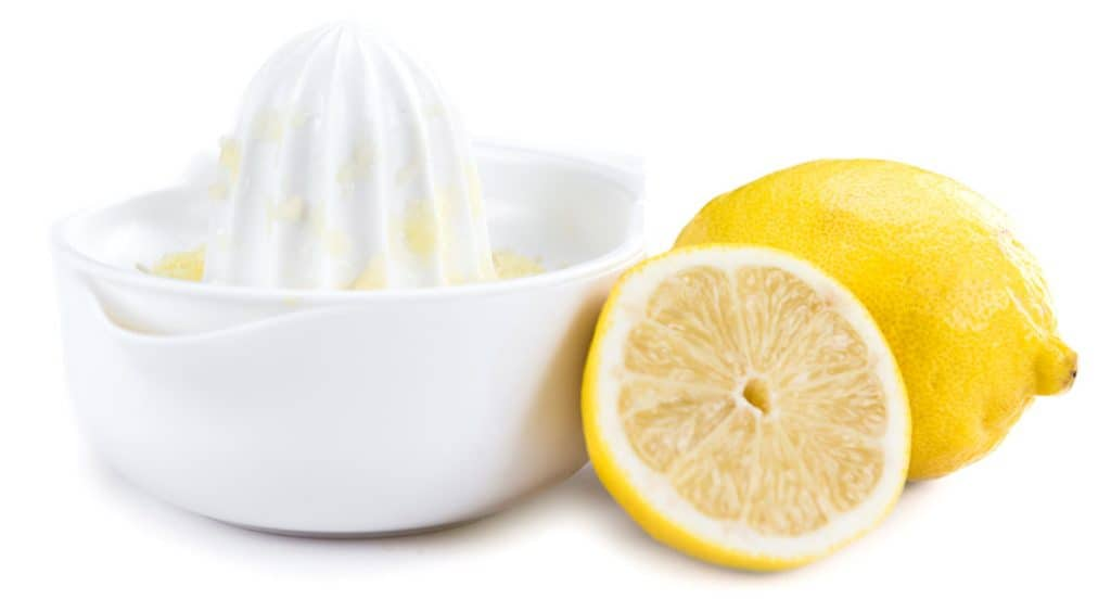 a lemon juicer with two lemon halfs next to it