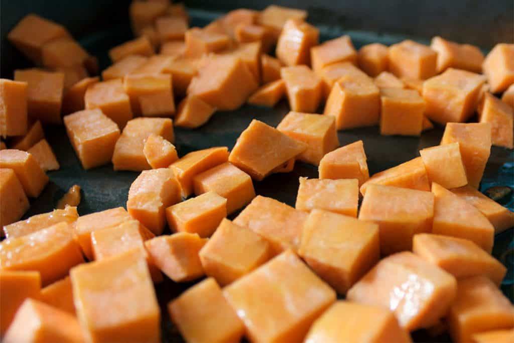 a cutting board with cubes of sweet potatoes