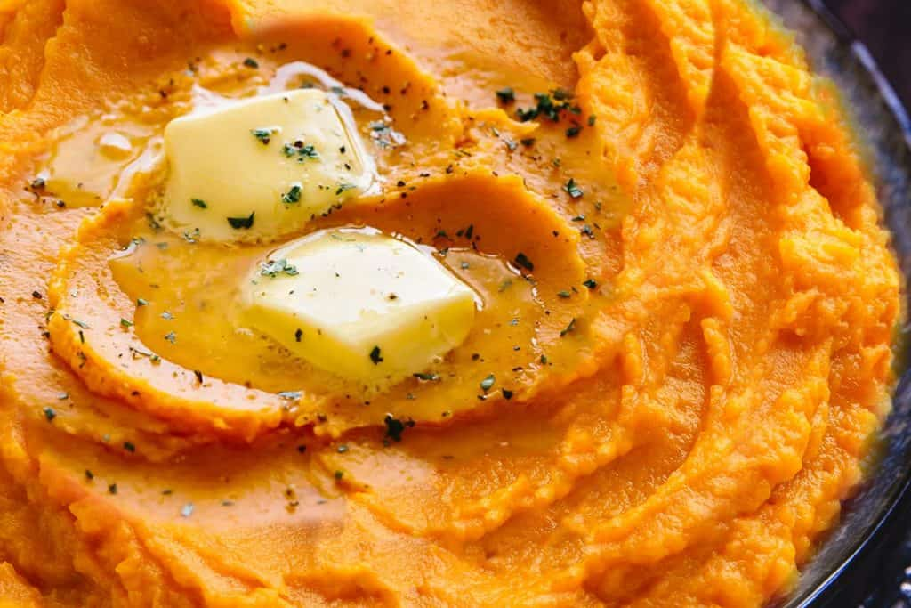 A close up of mashed sweet potatoes topped with butter and ground black pepper