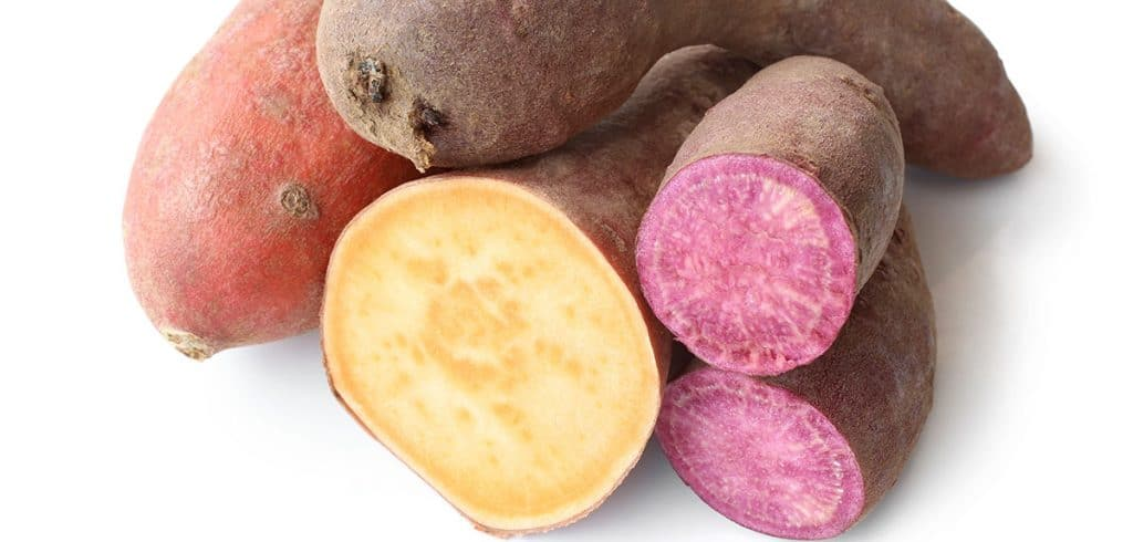 different types of sweet potatoes in a pile with some cut open to show purple and orange colors