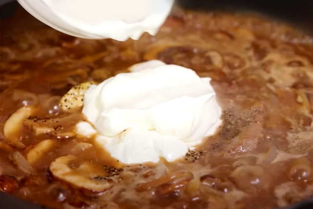 sour cream being added to the pan with the sauce