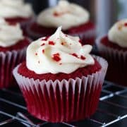 Red Cupcakes swirled with frosting and sprinkled with cake crumbs and more cupcakes in the background.