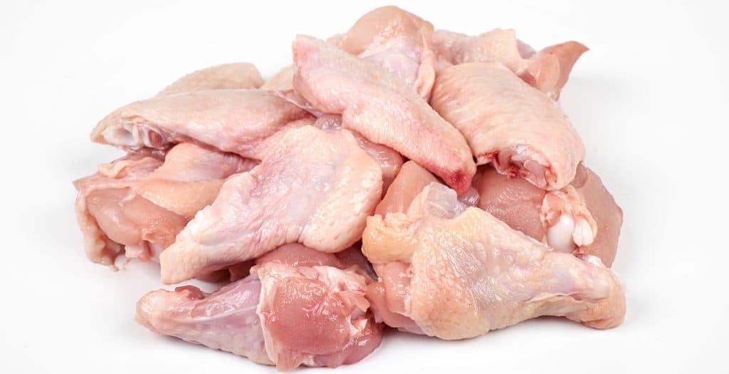 a pile of raw chicken wings with a white background