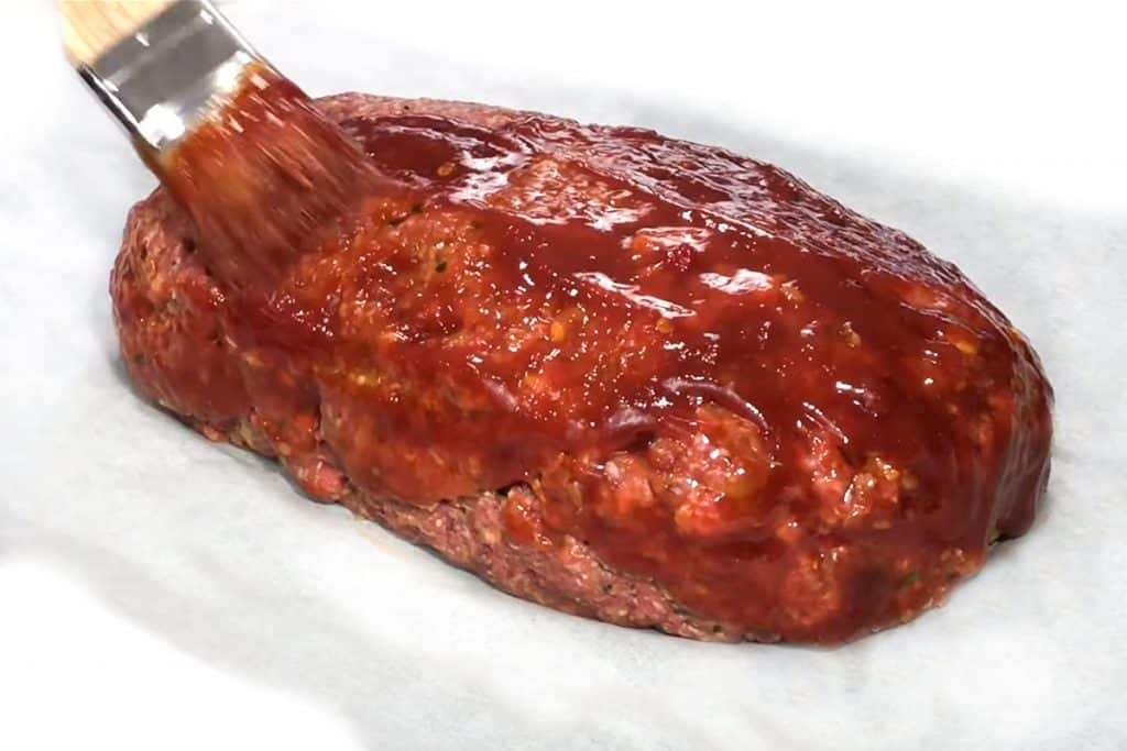 a brush adding the glaze to the raw meatloaf