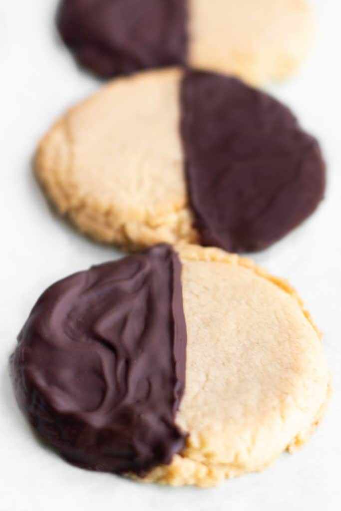 round shortbread cookies with half covered in chocolate