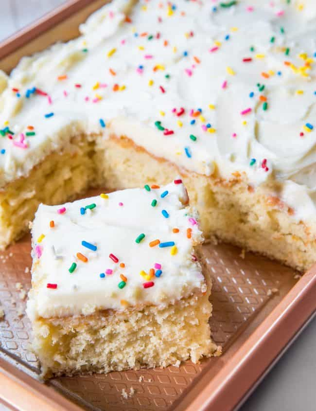 a sheet pan of vanilla cake with a slice cut out of it