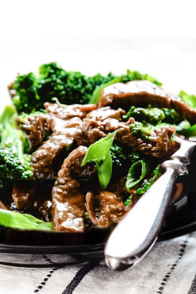 a plate of beef and broccoli with a brown sauce