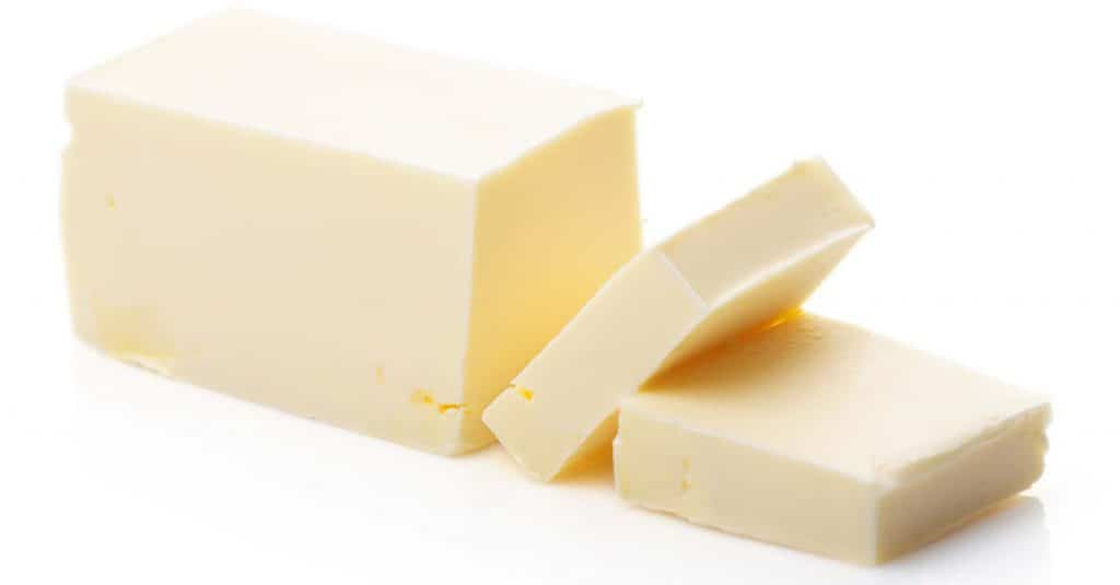a stick of butter with two slices cut