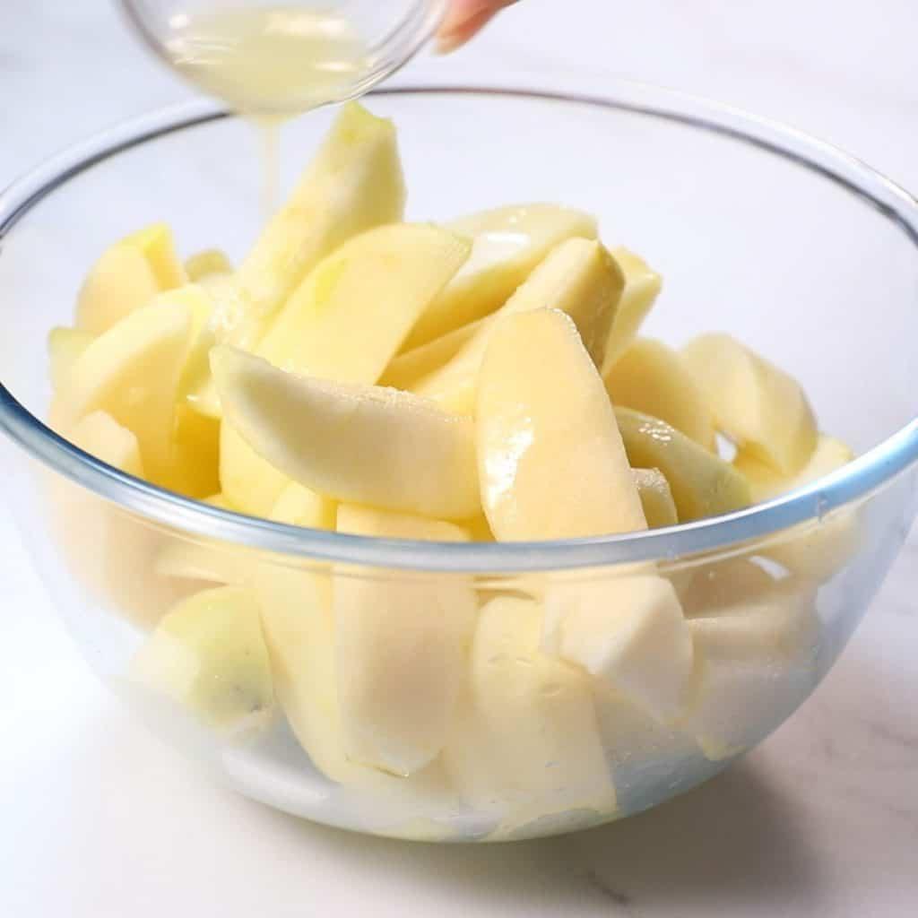Lemon Juice being poured over sliced apples