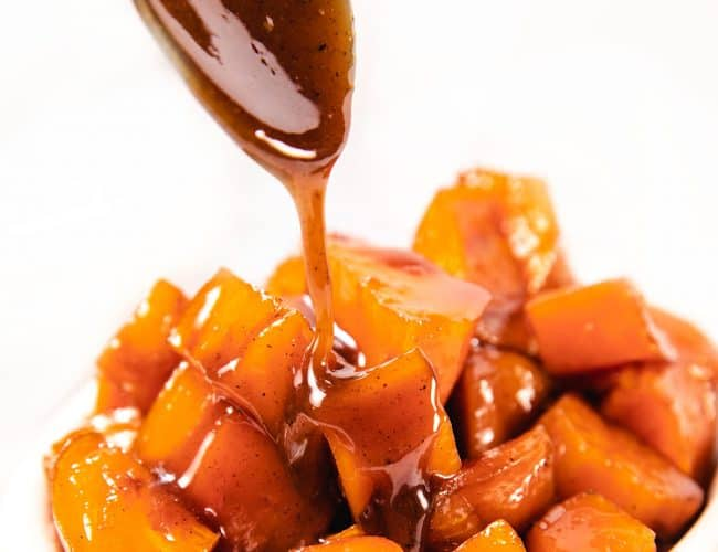 caramel sauce being spooned onto sweet potatoes