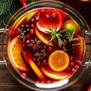 Christmas punch. Festive red cocktail, drink with cranberries and citrus fruits in a punch bowl and glasses