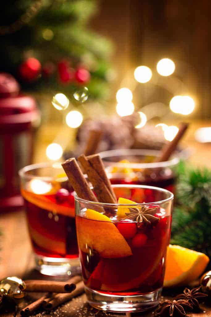 two glasses of Christmas Punch with festive lights in the background