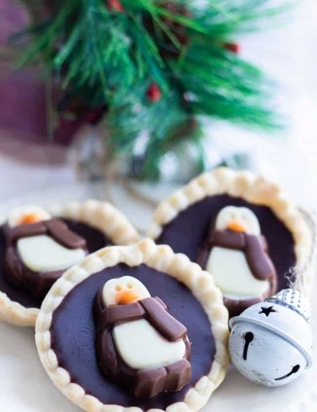 Three chcolate tarts on a plate with christmas decorations