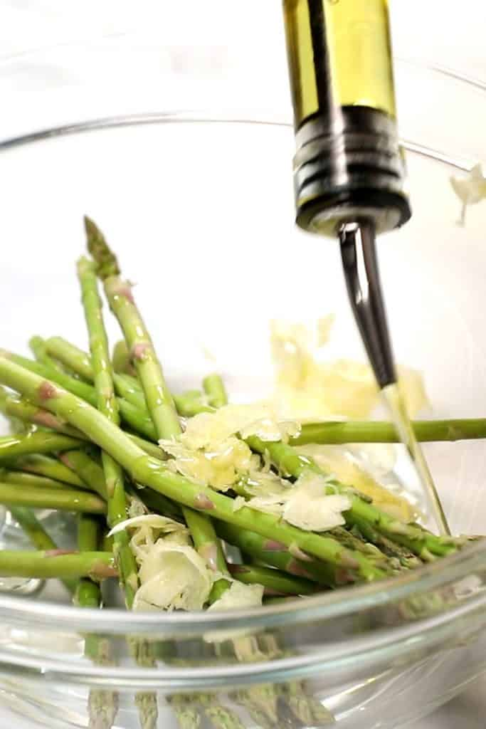 olive oil  being added to a bowl with asparagus