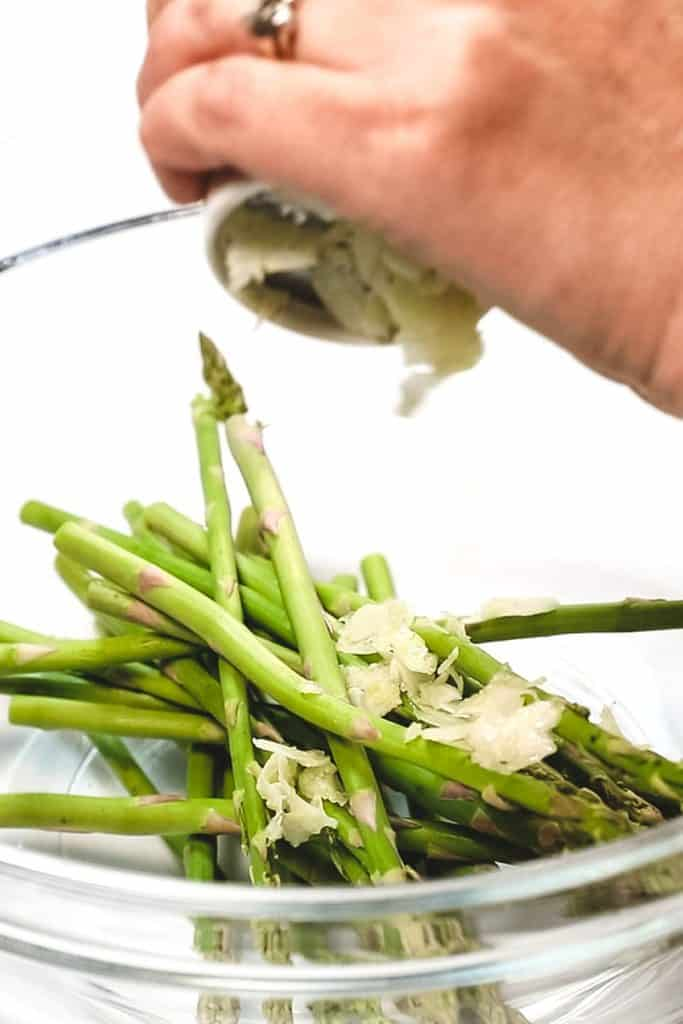 thin sliced garlic being added to a bowl with asparagus