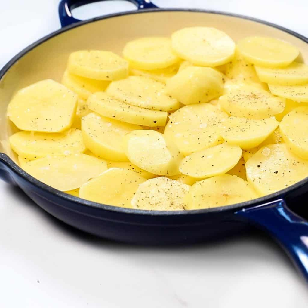 sliced potatoes added to a pan