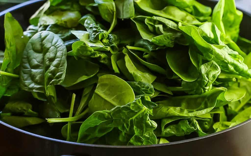 fresh spinach added to the pan with the sauce