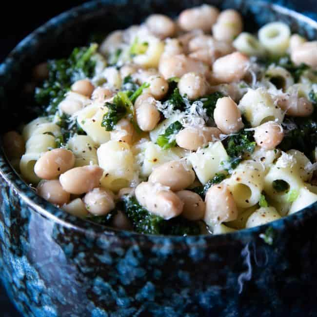 a bowl of white bean soup piled high with pasta and spinach