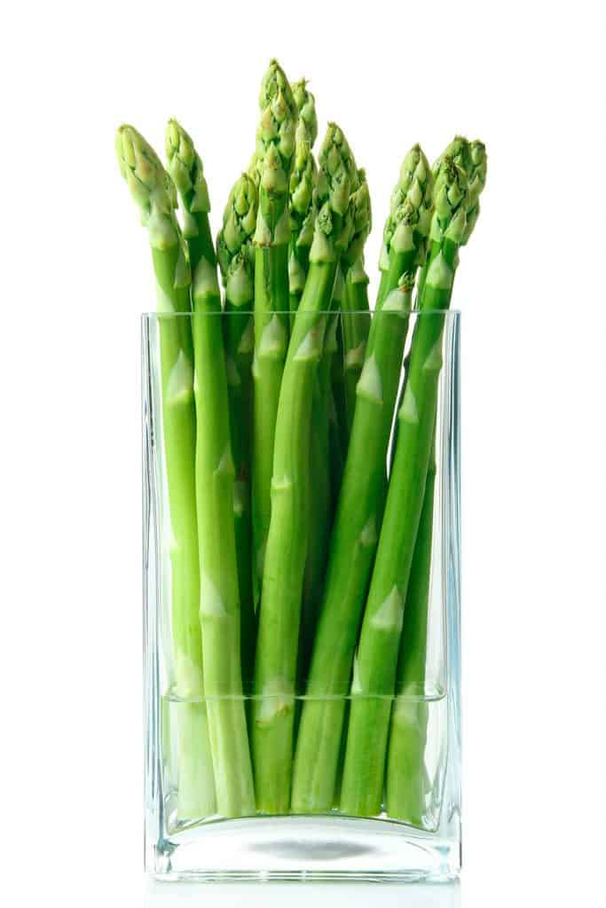asparagus standing up in a glass with water