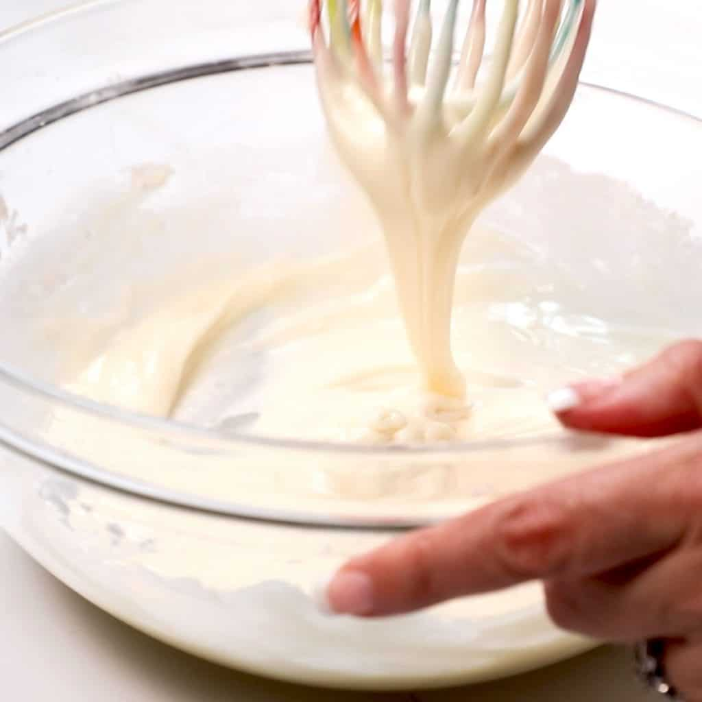 the icing being mixed with a whisk