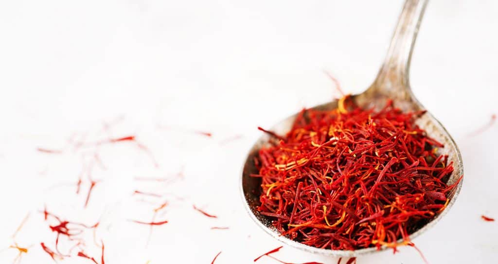Saffron threads in a rustic spoon isolated on white