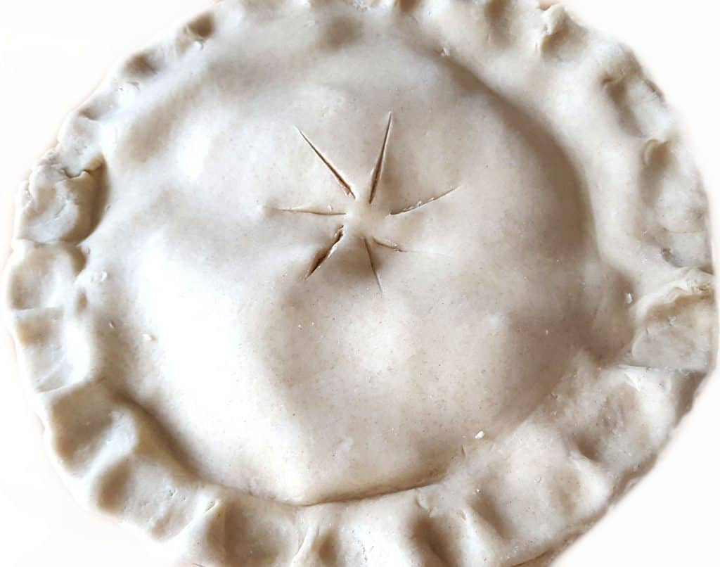 a raw apple pie with the top dough added to it