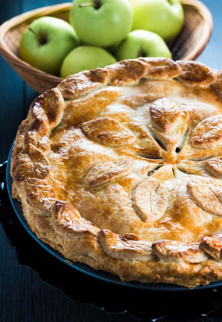 An apple pie fresh from the oevn with apples in the brackground