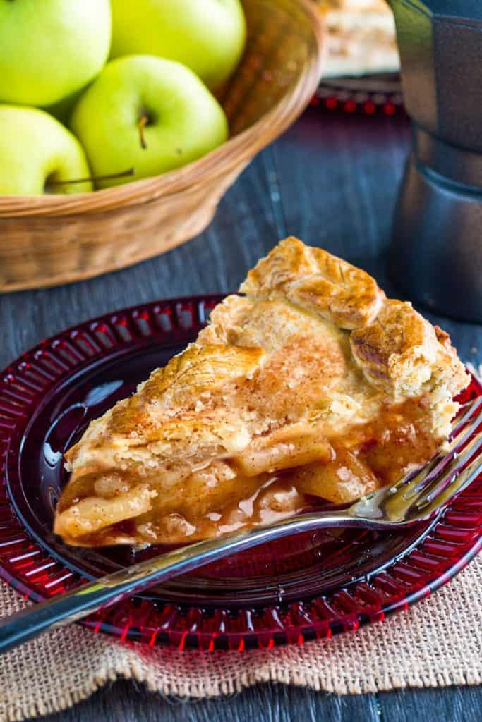 A slice of apple pie with a golen applie pie filling