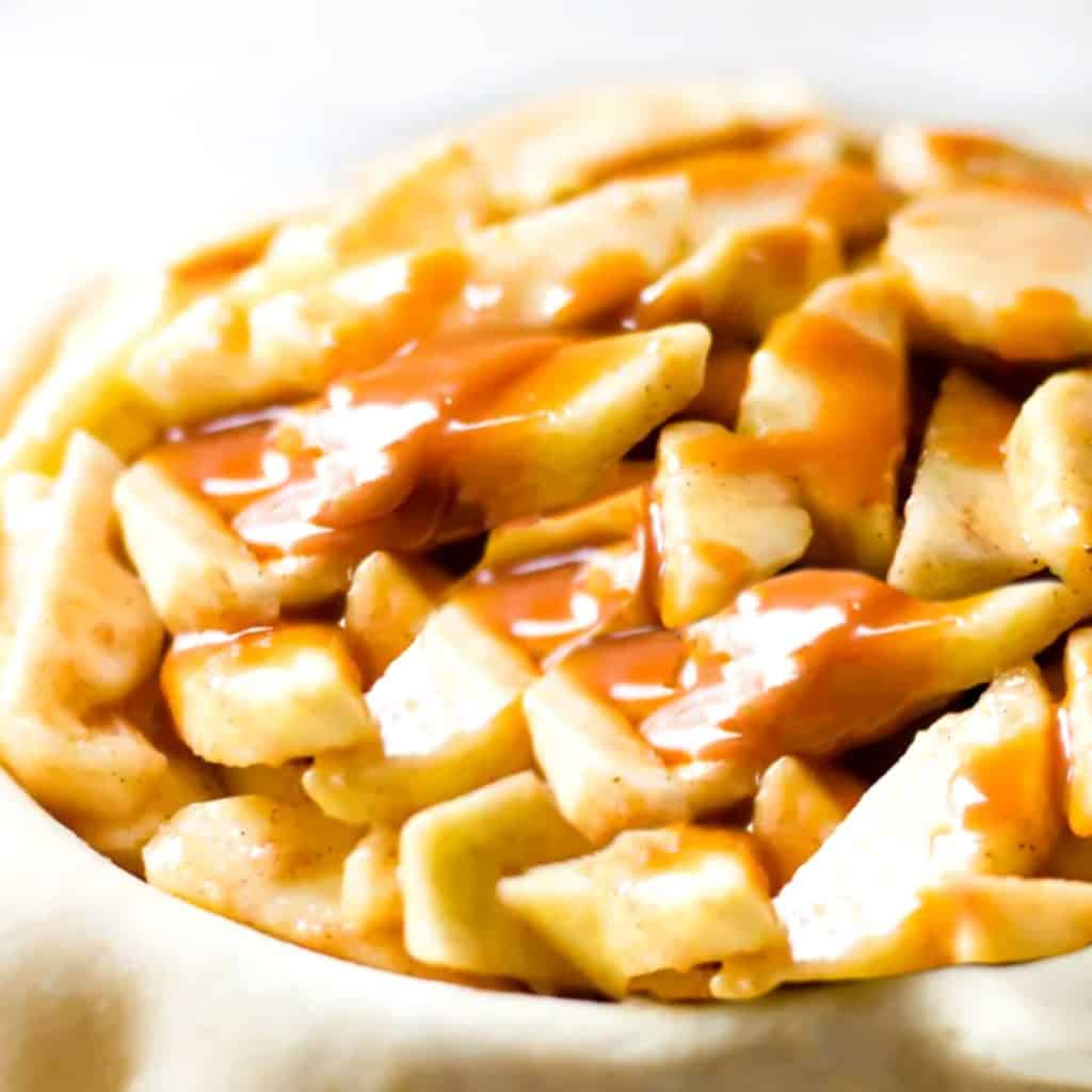sliced apples in pie dough with caranel sauce