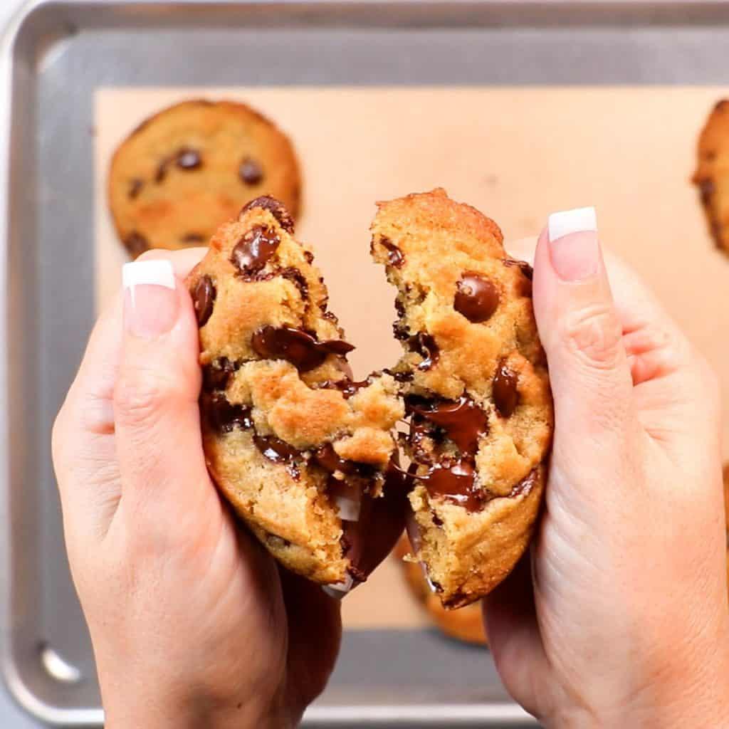 a warm chcolate chip cookie being broken in half