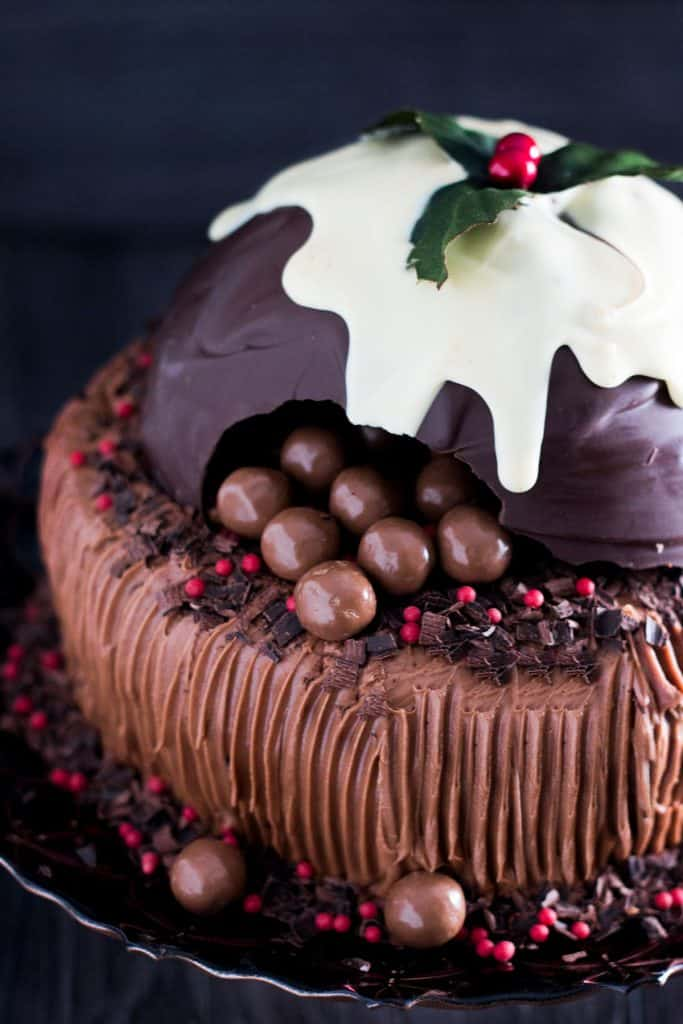 a chocolate cake topped with a christmas pudding made out of chocolate broken open to reveal candy inside