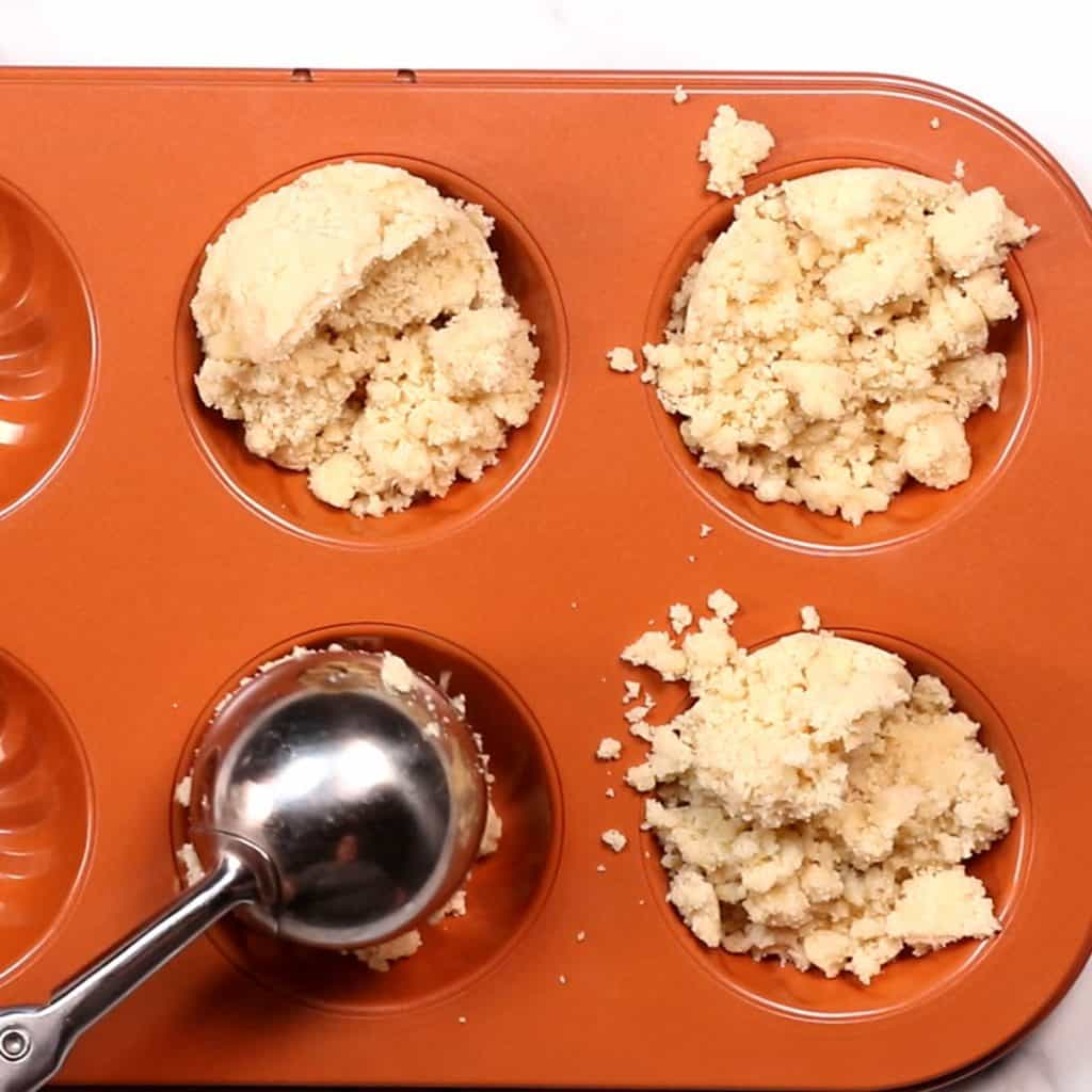 cookie dough being scooped into a mold.