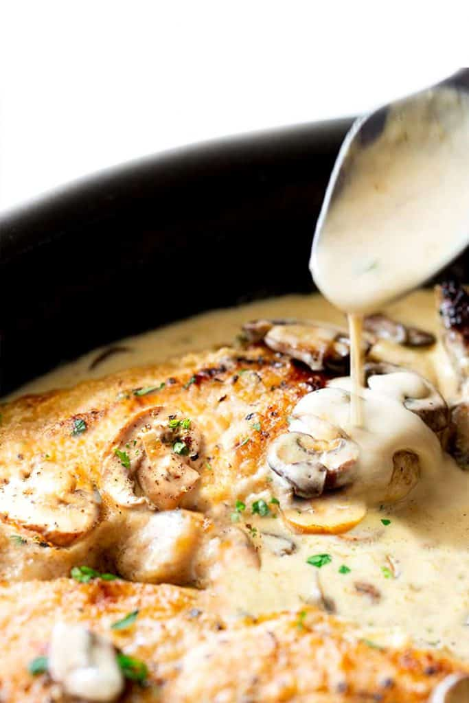 Creamy Mushroom Chicken in a skillet with a spoonful of sauce being served from it.