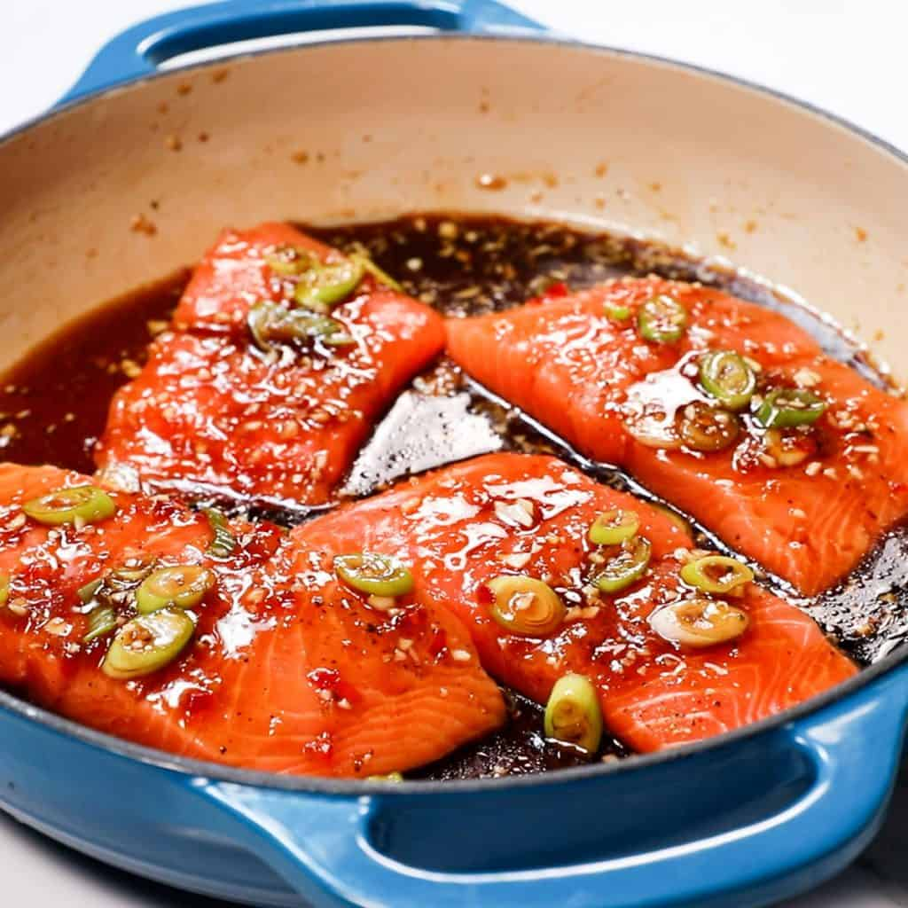 salmon in a pan with soy sauce, honey and green onions