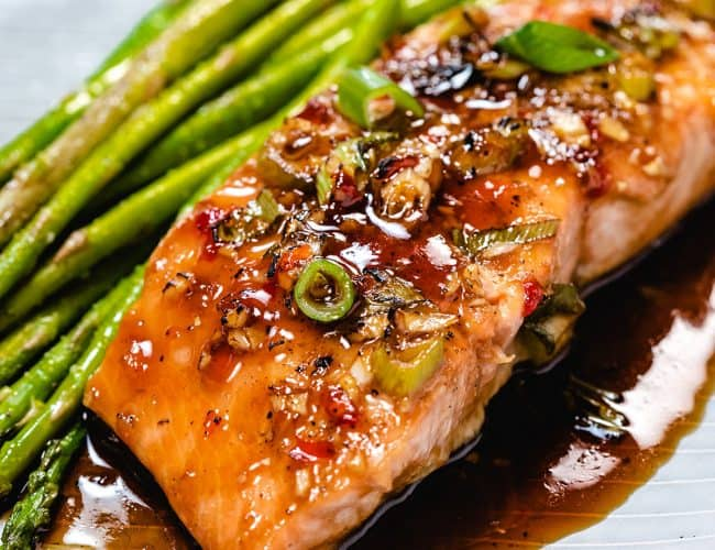 glazed salmon on a plate with asparagus next to it.