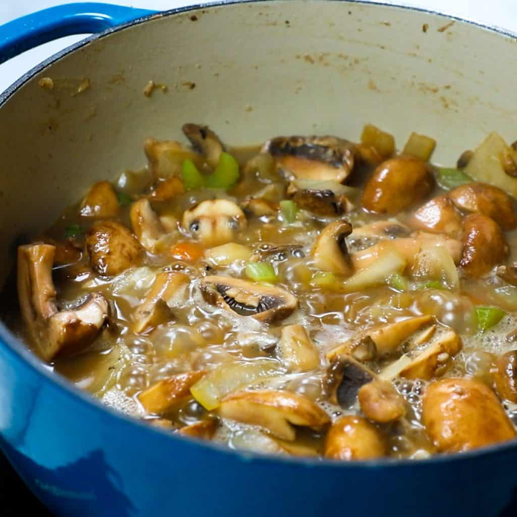 wine bubbling in the pan with the mushroom mixture